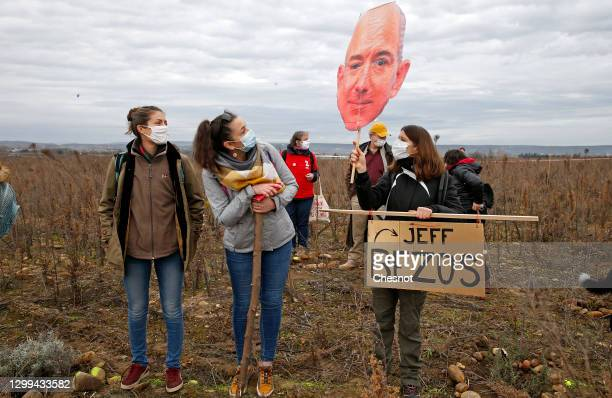 "An opponent holds a cutout sign depicting Amazon CEO Jeff Bezos, in front of a banner reading ""Stop Amazon"" during a rally against plans to build a..."