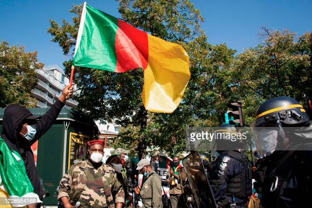 An opponent of current Cameroonian president waves a national flag in front of French riot policemen during a demonstration against Cameroon's...