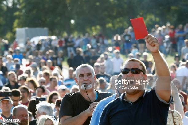 An opponent of German Chancellor Angela Merkel blows a whistle as another shows her the red card during an election campaign rally of the Christian...