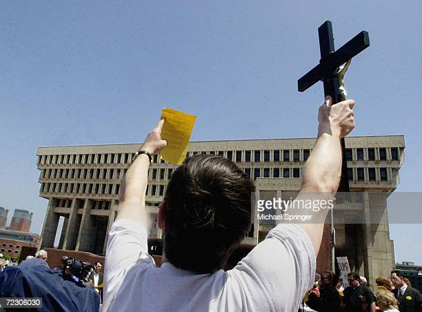 An opponent of samesex marriage holds up a crucifix and a sheet of paper with the lyrics of Battle Hymn of the Republic during a rally at City Hall...