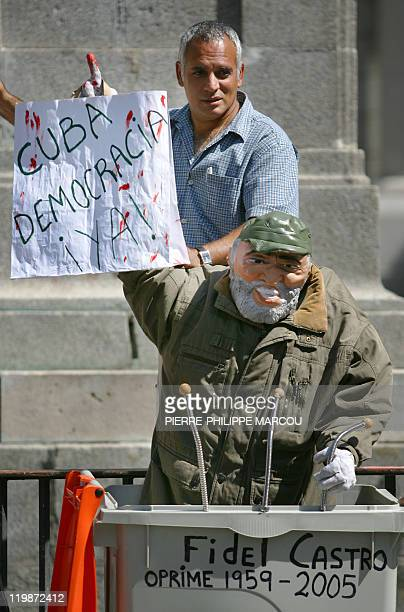 An opponent of the Cuban regime installs a doll representing Cuban President Fidel Castro underneath the spot where was once erected a statue of...