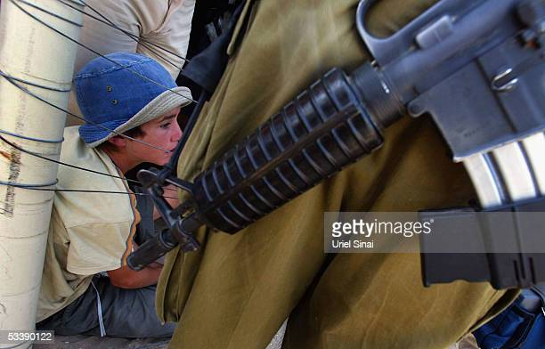 An opponent of the disengagement plan is seen behind an Israeli soldier as she sits behind the fence August 15 2005 in the Israeli settlement of Neve...