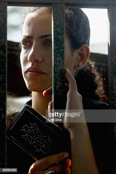 An opponent of the disengagement plan stands behind the locked gates August 15 2005 of the Israeli settlement of Neve Dekalim in the southern Gaza...