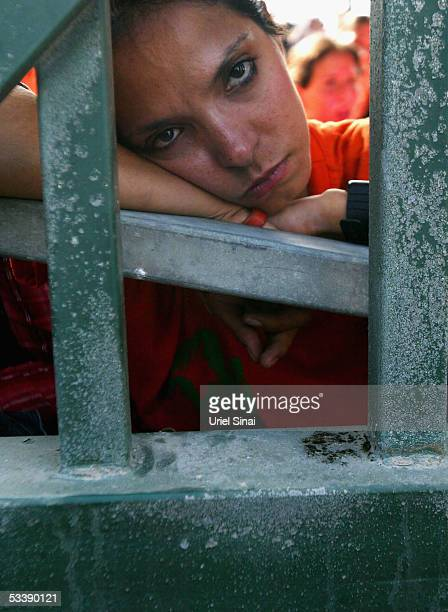 An opponent of the disengagement plan stands behind the locked gates August 15 2005 in the Israeli settlement of Neve Dekalim in southern Gaza Strip...