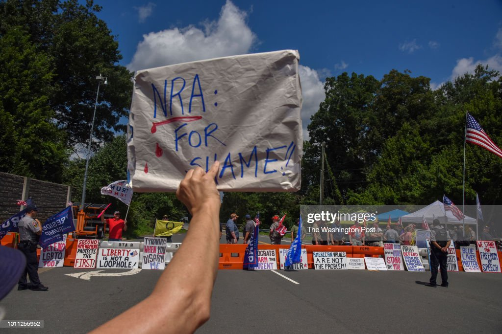 An opponent of the NRA holds a sign facing NRA supporters as various gun control organizations - including The National Organization For Change, March For Our Lives, and Team Enough - hold a demonstration on the street in front of the National Rifle Association (NRA) Headquarters in FairFax, VA, on Saturday, August 4, 2018, in Fairfax, VA. The 'March On NRA' is an event to highlight the battle faced by people of the United States as they seek to live in a world without the fear of gun violence. Included are organizations such as Youth Over Guns, WeCanVote, NoRA, Women's March, Gays Against Guns, MoveOn, Giffords Courage Fellowship, Guns Down, Families Belong Together and Youth Empower.