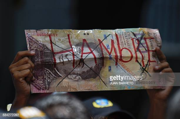An opponent to the government of Venezuelan President Nicolas Maduro holds a sign representing a Venezuelan currency bill reading 'Hunger' during a...