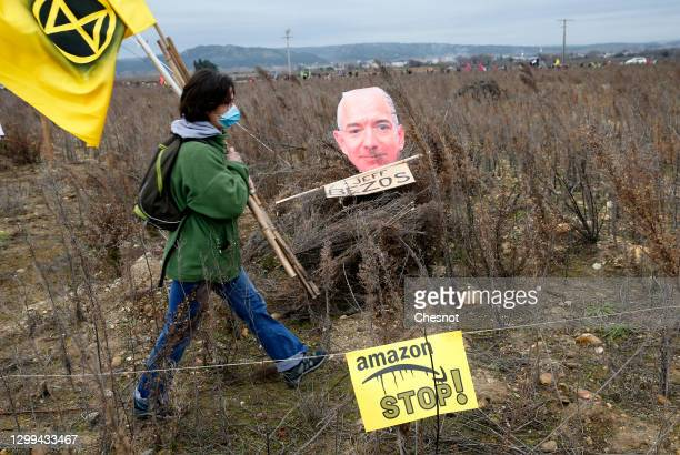 An opponent wearing a protective face mask walks past a cutout sign depicting Amazon CEO Jeff Bezos during a rally against plans to build a giant...