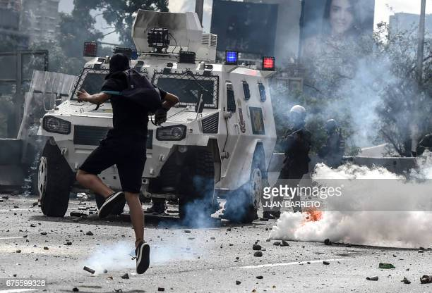 TOPSHOT An opposition activist clashes with the riot police during a march against Venezuelan President Nicolas Maduro held on May Day in Caracas on...