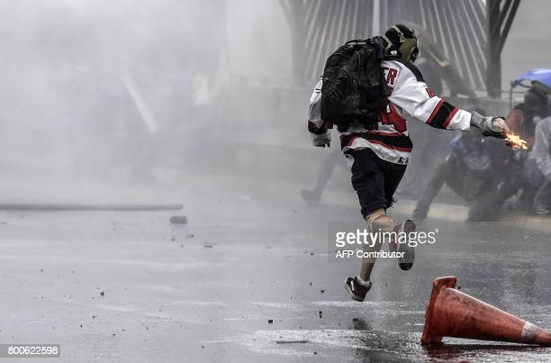 An opposition activist gets ready to throw a molotov cocktail during clashes with the police at the Francisco de Miranda air force base during a...