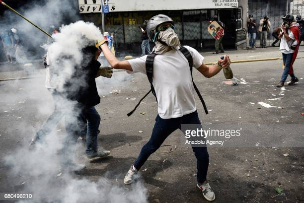 An opposition activist hurls back at riot police a tear gas canister during clashes ensuing a protest against President Nicolas Maduro in Caracas...