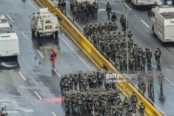TOPSHOT An opposition activist plays the violin in front of an armoured vehicle of the riot police during a protest against President Nicolas Maduro...