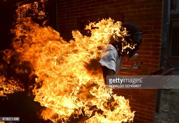 TOPSHOT An opposition activist suddenly turned into a human torch runs upon clashing with riot police during a protest against Venezuelan President...