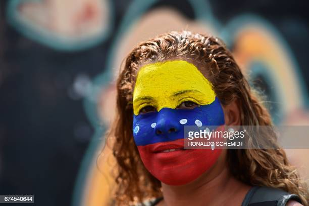 An opposition activist takes part in a protest march stopped by the National Guard 500 metres from the entrance to the Ramo Verde penitentiary in Los...
