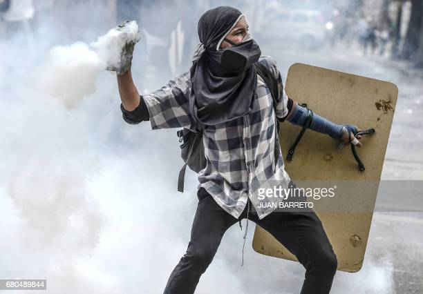 An opposition activist throws a Molotov cocktail at riot police during clashes ensuing a protest against President Nicolas Maduro in Caracas on May 8...