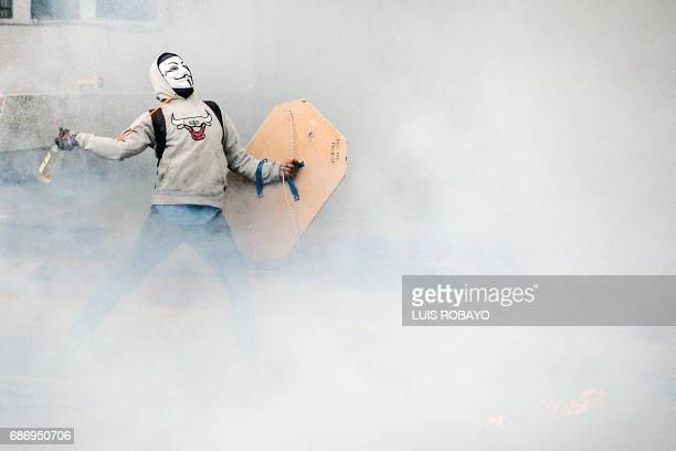 An opposition activist throws a molotov cocktail in clashes with riot police during a march by doctors and other health care personnel in Caracas...