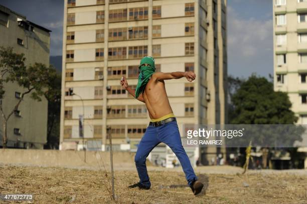 An opposition activist throws stones at the national police during a protest against the government of Venezuelan President Nicolas Maduro in Caracas...