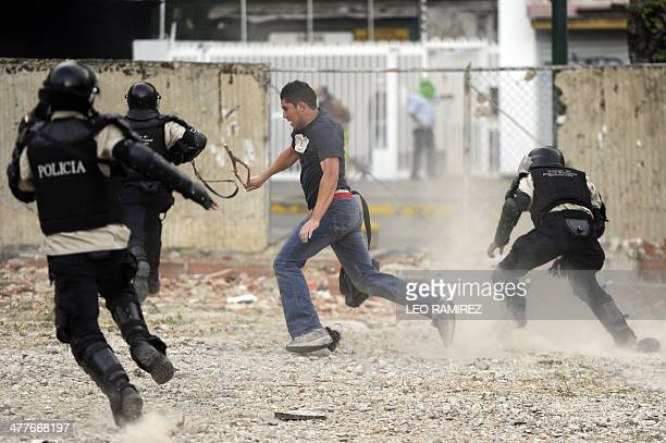 An opposition activist tries to escape from the national police during a protest against the government of Venezuelan President Nicolas Maduro in...