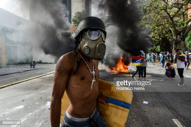 TOPSHOT An opposition activist wearing a helmet and gas mask stands near a burning motorbike during a protest against the government of Nicolas...