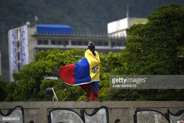 TOPSHOT An opposition activist wrapped in the national flag stands on a wall during a demonstration against the government of Venezuelan President...