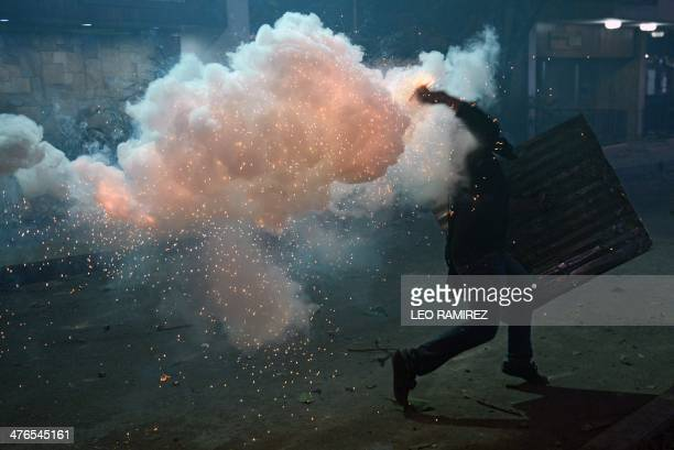 An opposition activists hurls a home made explosive device to National Guard troops during a protest against the government of Venezuelan President...
