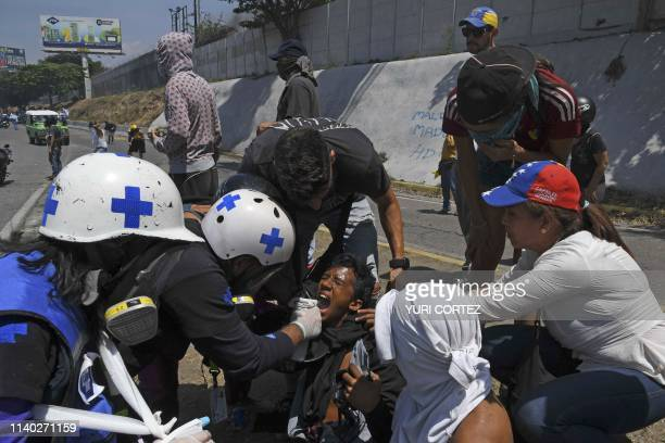 An opposition demonstrator affected by tear gas is assisted during clashes with soldiers loyal to Venezuelan President Nicolas Maduro after troops...