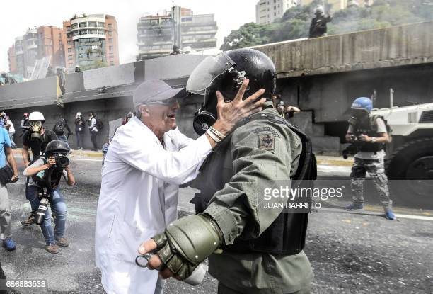 TOPSHOT An opposition demonstrator argues with a National Guard riot policeman during a health care personnel march in Caracas on May 22 2017 Doctors...