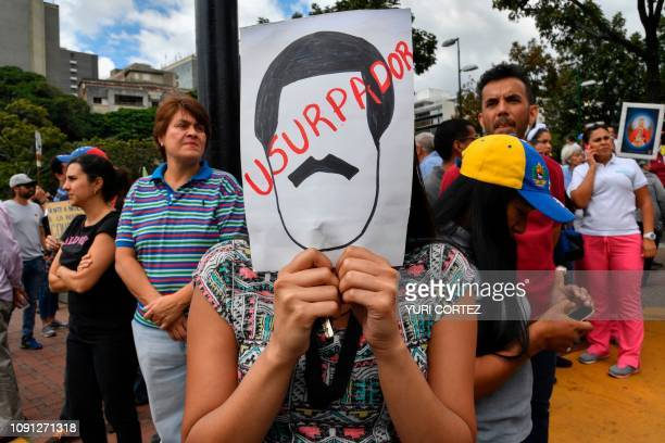 """An opposition demonstrator holds a sign depicting the face contour of Venezuelan President Nicolas Maduro with a legend reading """"Usurper"""", during a..."""