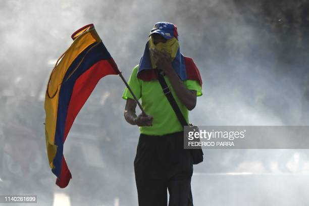 An opposition demonstrator holds a Venezuelan flag after members of the Bolivarian National Guard joined Venezuelan opposition leader and...