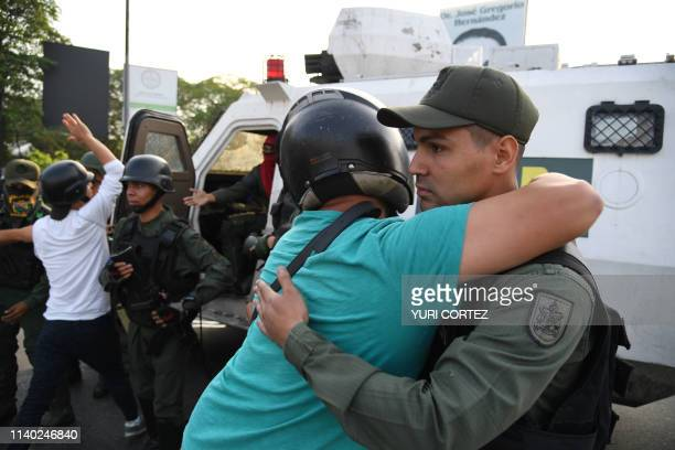 An opposition demonstrator hugs a member of the security forces in Caracas on April 30, 2019. - Venezuelan opposition leader and self-proclaimed...