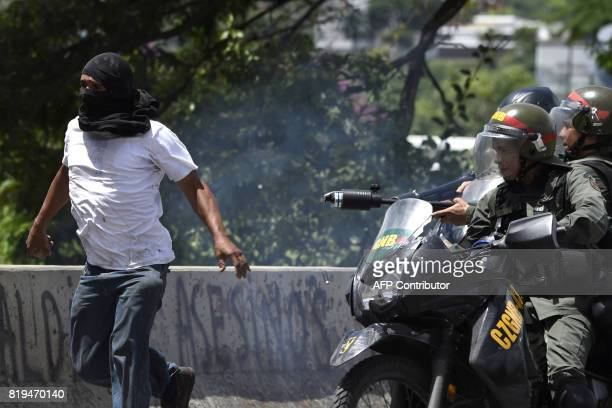 TOPSHOT An opposition demonstrator is chased by National Guard motorcyclists in riot gear during an antigovernment protest in Caracas on July 20 2017...