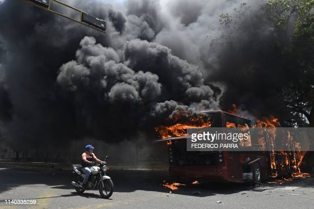 An opposition demonstrator passes by a government bus set on fire during clashes with soldiers loyal to Venezuelan President Nicolas Maduro after...
