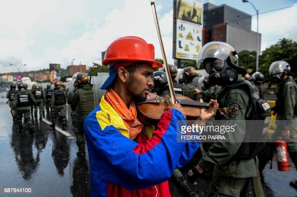 An opposition demonstrator plays the violin during a protest against President Nicolas Maduro in Caracas on May 24 2017 Venezuela's President Nicolas...