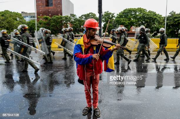 TOPSHOT An opposition demonstrator plays the violin during a protest against President Nicolas Maduro in Caracas on May 24 2017 Venezuela's President...