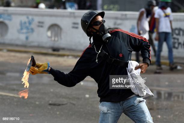 An opposition demonstrator throws a molotov cocktail at riot police as they clash with the Bolivarian National Guard during a protest against the...