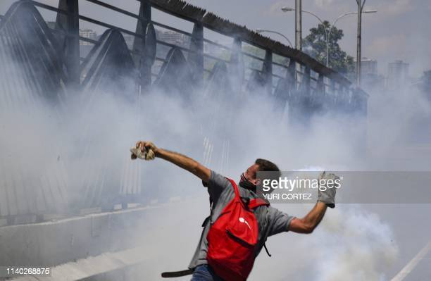 An opposition demonstrator throws a tear gas canister during clashes with soldiers loyal to Venezuelan President Nicolas Maduro after troops joined...