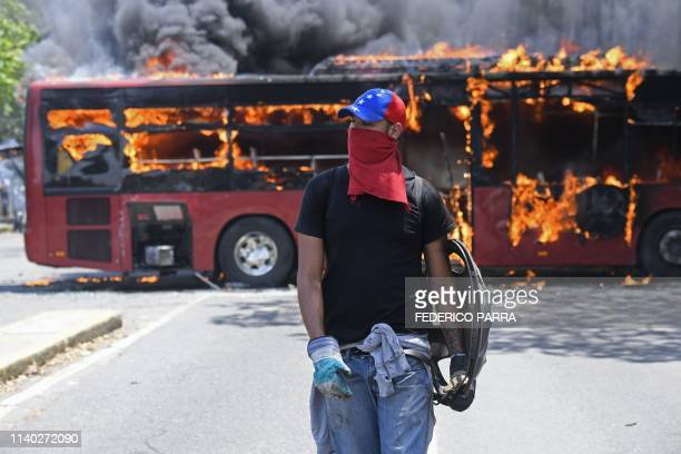 TOPSHOT An opposition demonstrator walks near a bus in flames during clashes with soldiers loyal to Venezuelan President Nicolas Maduro after troops...