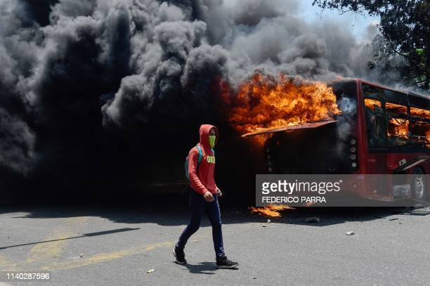 An opposition demonstrator walks near a bus in flames during clashes with soldiers loyal to Venezuelan President Nicolas Maduro after troops joined...