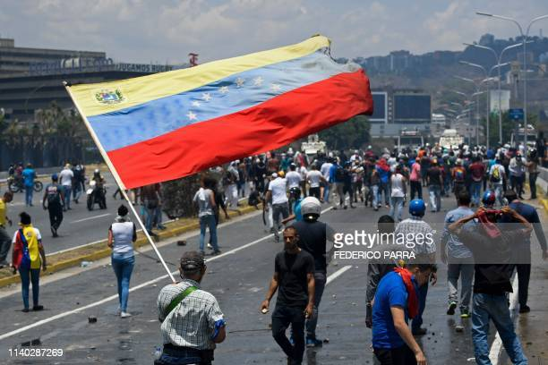 An opposition demonstrator waves a Venezuelan national flag during clashes with soldiers loyal to Venezuelan President Nicolas Maduro after troops...