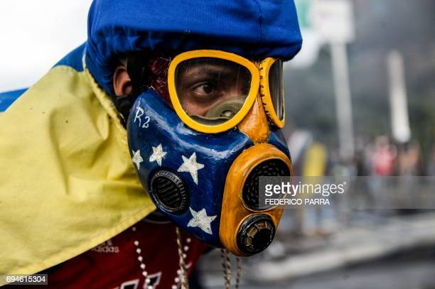 TOPSHOT An opposition demonstrator wears a gas mask in a clash with police during the 'Towards Victory' protest against the government of President...