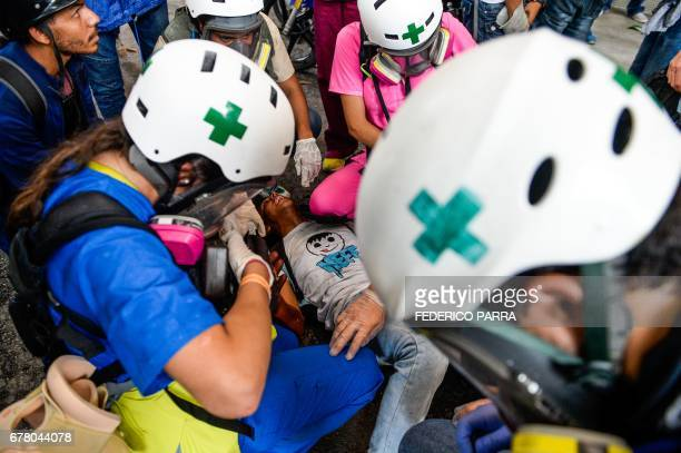 TOPSHOT An opposition demonstrator wounded during clashes with riot police is assisted by medics during a protest against Venezuelan President...