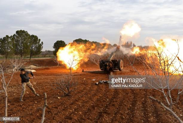 An opposition fighter fires a gun from a village near al-Tamanah during ongoing battles with government forces in Syria's Idlib province on January...