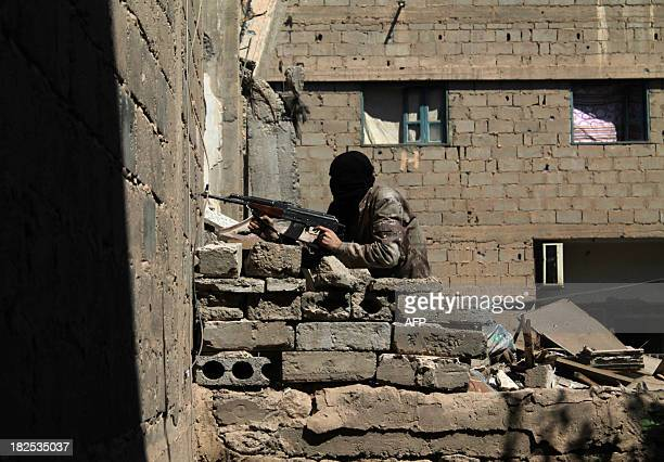 An opposition fighter guards a position in the Jubaila neighbourhood of Syria's northeastern city of Deir Ezzor on September 30 2013 as the violence...