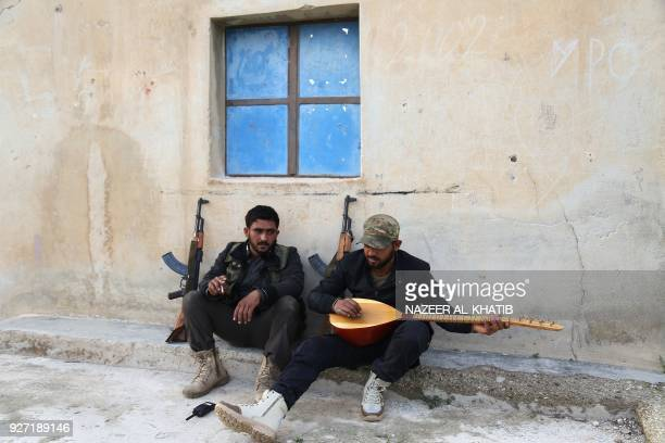 TOPSHOT An opposition fighter plays an oud after they took control of the village of Ali Bazan on the eastern bank of Lake Maydanki north of the...
