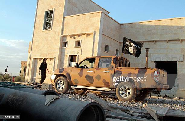 An opposition fighter walks near a vehicle flying a black Jihadist flag with Islamic writing on it proclaiming in Arabic that 'There is no God but...