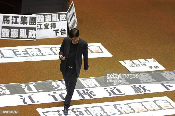 An opposition legislator walks over placards displayed on the floor at the Parliament on September 17, 2013 in Taipei, Taiwan. Taiwan's President Ma...