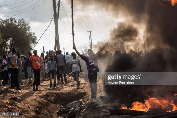 An opposition protestor dances in front of a flaming roadblock in the Kawangware slum on October 27 2017 in Nairobi Kenya Protests continued in...