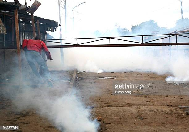 An opposition protestor runs for shelter as Kenyan security forces fire tear gas during streets riots in the suburbs of Mathare in Nairobi Kenya on...