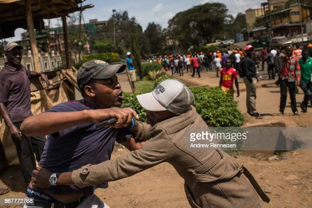 An opposition supporter grabs a man he believed to support Jubilee President Uhuru Kenyatta's political party on October 29 2017 in Nairobi Kenya...