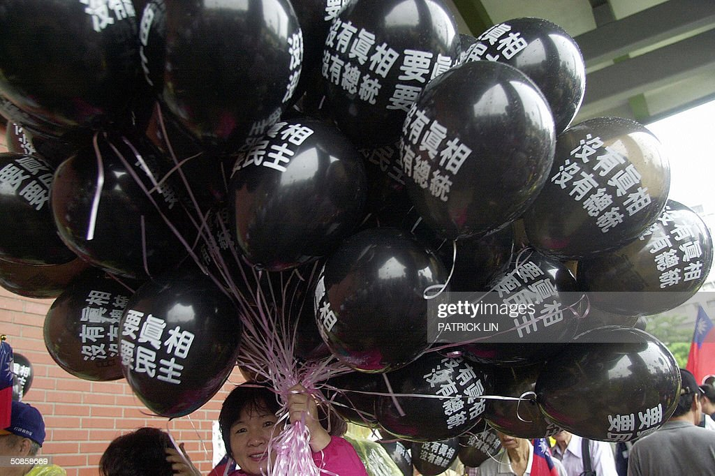 An opposition supporter holds a bundle of balloons with a protest slogan of 'truth' during a protest rally in Taipei, 20 May 2004 as President Chen is sworn in for a second four-year term. The opposition is disputing Chen's re-election claiming it was the result of unfair election. Chen won the 20 March presidential polls by a razor-thin margin of 0.22 percent, or 30,000 votes.