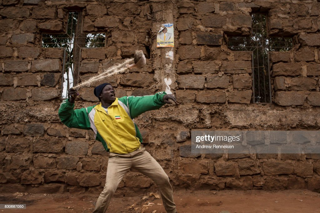 An opposition supporter shoots a slingshot at Kenyan police forces as the two sides clashed in the Kibera slum on August 12, 2017 in Nairobi, Kenya. Demonstrations turned violent in some areas throughout Kenya after Uhuru Kenyatta was named to his second term in Kenya's 2017 presidential election.